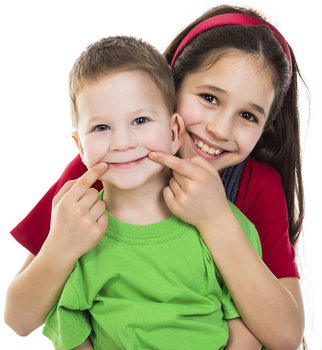 Image of two kids smiling. Learn more about how fluoride and sealants can help protect your smile at Fox Dental Excellence in Mason, OH